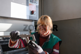 a woman working in a modern factory for the production and processing of metals, preparing and measures materials that go to the processing of CNC machines