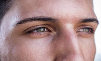 Close-up of green eyes of a handsome young man