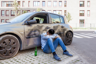 man with damaged automobile with scratches and dents