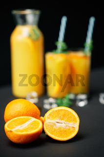 Delicious fresh orange juice with ice, mint and fruits on black table background.