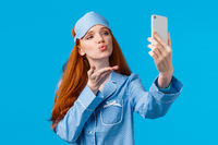 Waist-up portrait charming feminine redhead female in cute pyjama, saying followers goodnight, telephone addicated, taking selfie, blow air kiss to camera, standing blue background