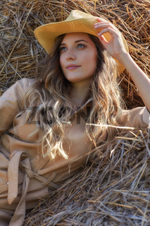 Young blonde woman in a beige jumpsuit is sitting on the rolls of hay.