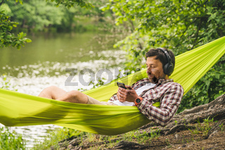 Man travels on bicycle, relaxing in green hammock, surfing Internet on smartphone, listening music on headphones in forest near lake. Cyclist in hammock at campsite by river. Male on bike in hammock