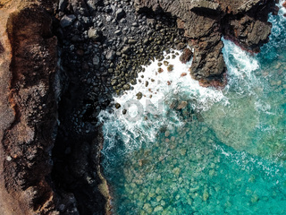 Aerial view of rocks and sea waves in a volcanic landscape with lava