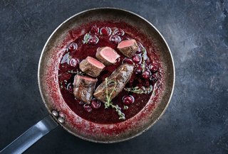 Traditional wild hare back filet braised with wild berries and cherry relish souse served as top view in rustic frying pan on an old black board