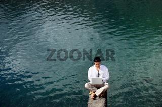Businessman sat by lake