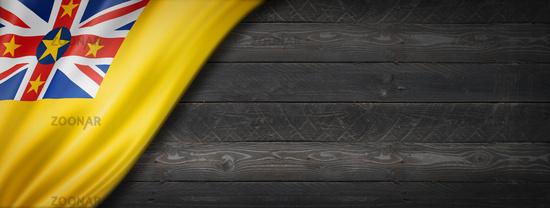 Niue flag on black wood wall banner