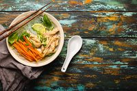 Asian soup with noodles in bowl top view copy space