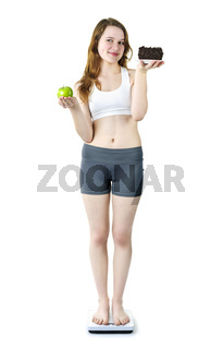Young girl on scale holding apple and cake