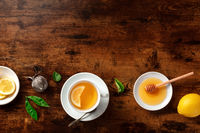 Tea with lemons and honey, shot from the top on a rustic background