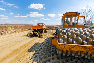 Road roller with spikes and truck plate compactor are working at construction site