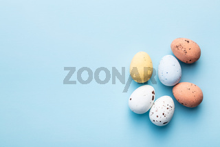 Colorful chocolate easter eggs. Sweet candy eggs on blue background.