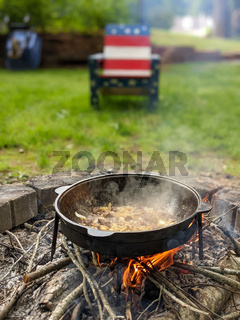 gourmet beef stew cooked in cauldron on outdoor fire pit