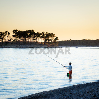 Man fishing on the shore of adriatic sea on island rab