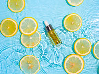 Cosmetic bottle in water, lemon slices, blue