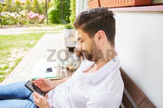 Mann mit Smartphone liest SMS auf der Terrasse