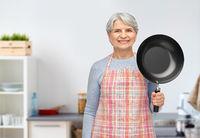 smiling senior woman with frying pan at kitchen