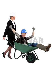 businesswoman carrying a craftswoman in a wheelbarrow