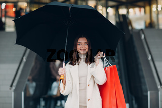 Positive young adult woman carrying paper shopping bags and umbrella in hands
