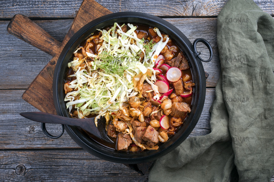 Traditional slow cooked Mexican pozole rojo soup with pork meat and hominy maiz served as top view in a modern design cast-iron roasting dish on an old rustic wooden board