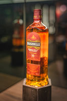 Rare, aged 16 year Bushmills whiskey on illuminated display in distillery shop