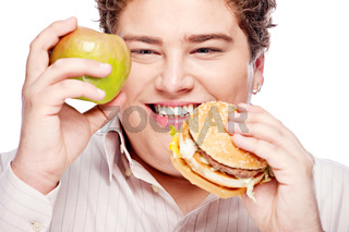 chubby man holding apple and hamburger