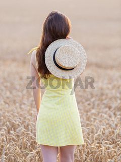Beautiful young woman in a yellow dress on a golden wheat field at sunset. The girl holds a straw hat in her hands