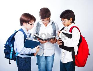 Three cute schoolboys read books