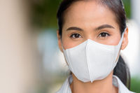 Close-up headshot of Asian woman wearing face mask to protect from coronavirus Covid-19