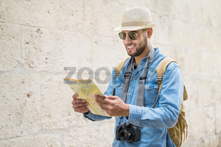 Young handsome man with tourist map looking around the city street.