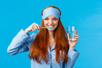 Enthusiastic upbeat, lively redhead woman, foxy girl with pretty smile, brushing teeth holding toothbrush and glass water, wake up morning, getting dressed, wearing sleep mask and pyjama