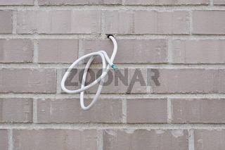 electrical wire or power cable hanging from exterior wall