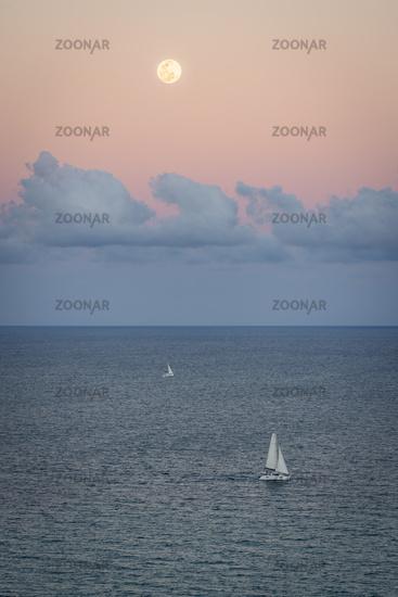 A beautiful setting moon over a sailboat and the Atlantic Ocean. Florida, USA.