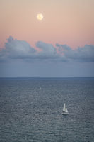 A beautiful setting moon over a sailboat and the Atlantic Ocean. Florida, USA.