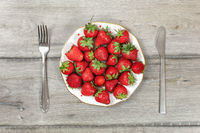 Tabletop view, plate with strawberries on gray wood boards desk, fork and knife next to it - ready to eat healthy snack concept.