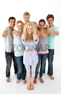 Group of teenagers standing in front of the camera with thumbs up