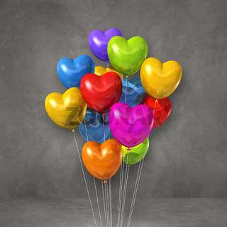 Colorful heart shape balloons bunch on a grey wall background