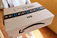 Courier hands holding Amazon premium Prime carton parcel box