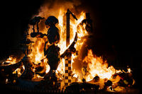 Burning paper mache figurines with silhoutte of a granny at the Fallas festival in Gandia, Spain