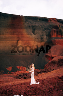 Portrait of a bride model in a golden wedding evening dress, in a yellow-red sandy quarry, in the crater of a volcano in Iceland, Golden Circle. Bouquet of snags and golden branches.