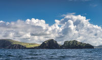 Majestic Kerry Cliffs with fields on the top, seen from a boat on Atlantic Ocean
