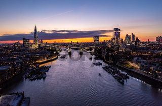 Aerial view of the famous Tower Bridge over ocean surrounded with buildings and skyscrapers under a cloudy twilight and dusk orange morning sky