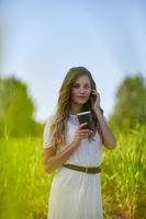 Young blonde woman in white dress with coffee cup is standing in a tall grass..