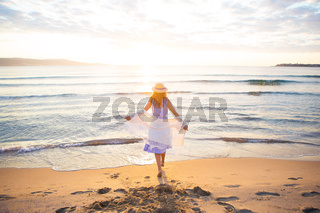 Young woman in blue dress walking barefoot on the beach, sunrise