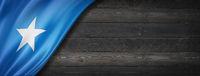 Somalian flag on black wood wall banner