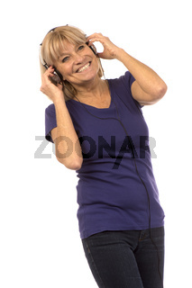 Senior woman 50-60years listening to music with stereo headphones on white.