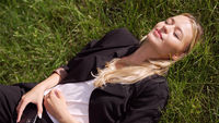 Businesswoman lying on grass in park