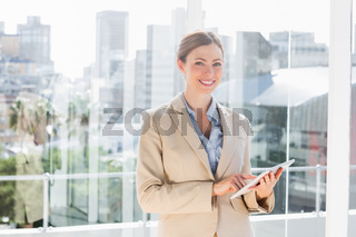 Pretty businesswoman using her tablet pc and smiling at camera
