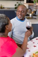 Happy african american senior couple making toast with wine, having christmas meal at home