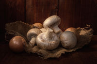 mushrooms on a burlap napkin on a dark wooden background in a rustic style